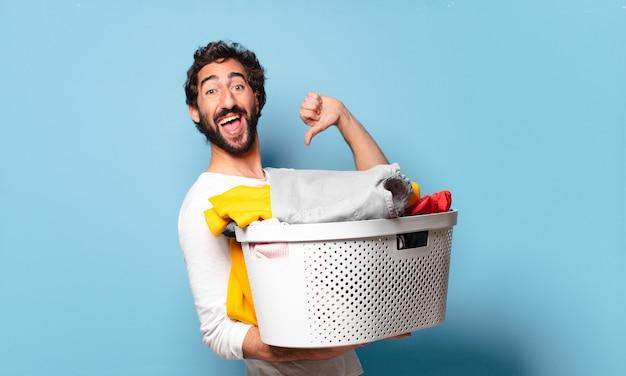 Młody szalony brodaty mężczyzna sprzątający pranie ubrań