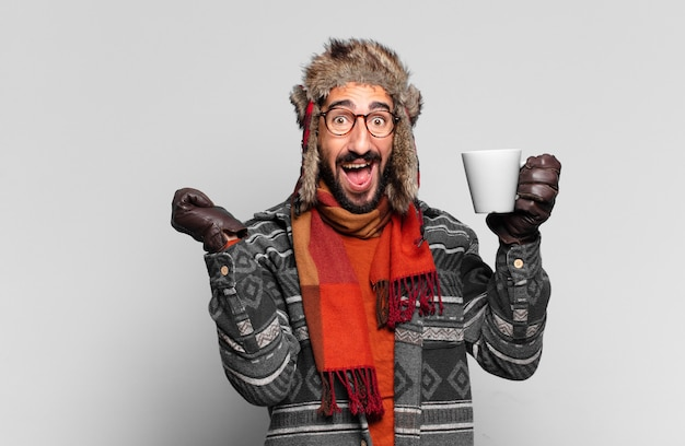 Młody szalony brodaty mężczyzna świętujący triumf jak zwycięzca i ubrany w zimowe ubrania