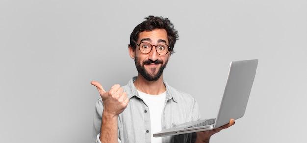Młody szalony brodaty mężczyzna. szczęśliwy i zaskoczony wyraz twarzy. koncepcja laptopa
