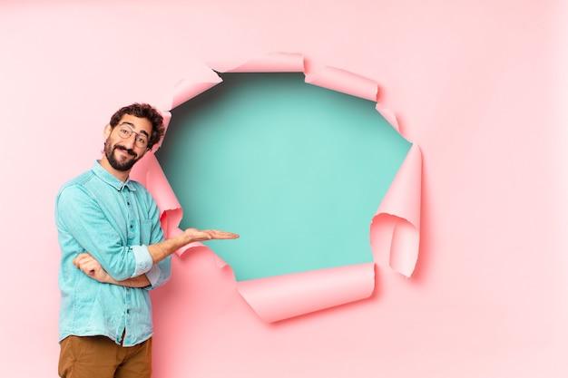 Młody szalony brodaty mężczyzna. szczęśliwy i zaskoczony wyraz twarzy. papierowa dziura pusta koncepcja tła