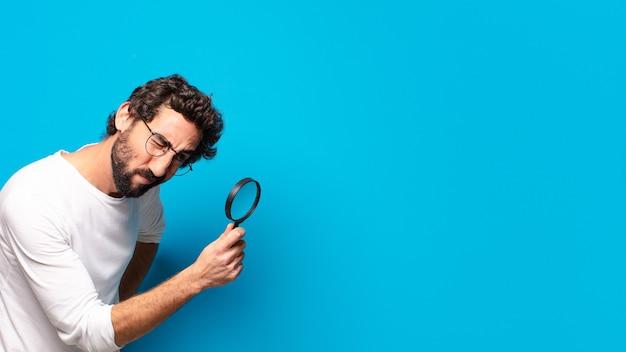 Młody szalony brodaty mężczyzna szuka i próbuje znaleźć za pomocą lupy