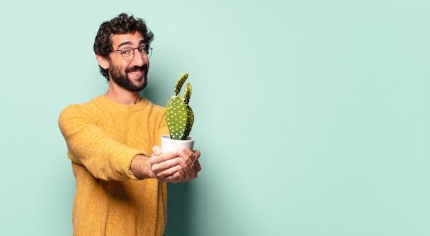 Młody szalony brodaty mężczyzna trzyma kaktusową roślinę domową