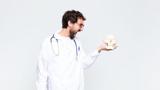 Młody szalony brodaty mężczyzna trzyma ludzką czaszkę