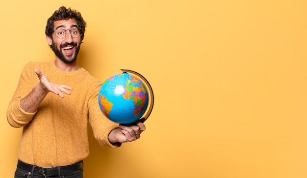 Młody szalony brodaty mężczyzna trzyma mapę świata.