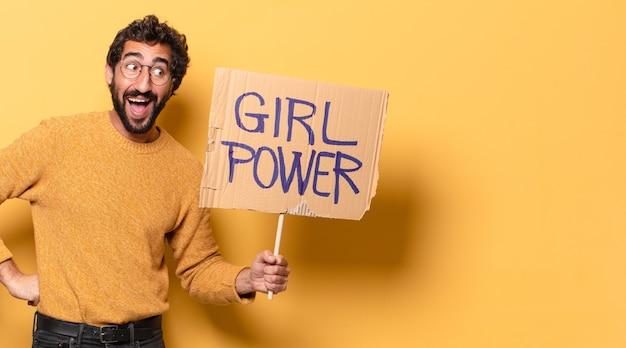 Młody szalony brodaty mężczyzna trzyma sztandar dziewczyna moc
