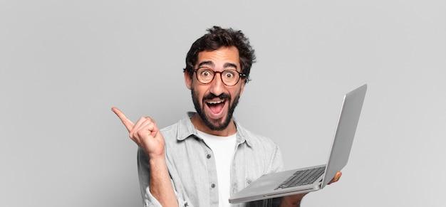 Młody szalony brodaty mężczyzna trzymający laptopa ze zszokowanym wyrazem twarzy