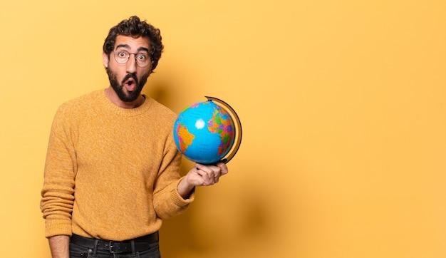 Młody szalony brodaty mężczyzna trzymający mapę świata globe