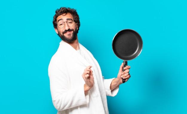 Młody szalony brodaty mężczyzna ubrany w szlafrok, gotowanie na patelni