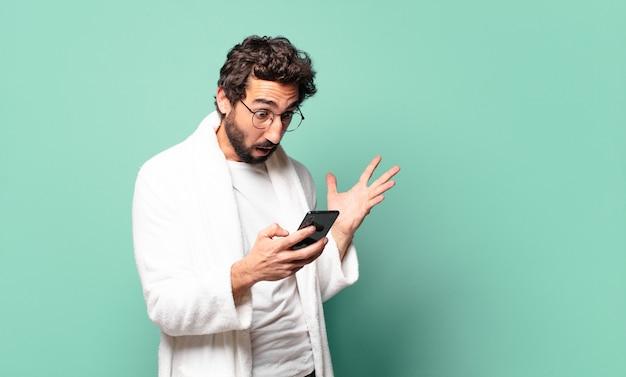 Młody szalony brodaty mężczyzna ubrany w szlafrok przy użyciu swojej komórki