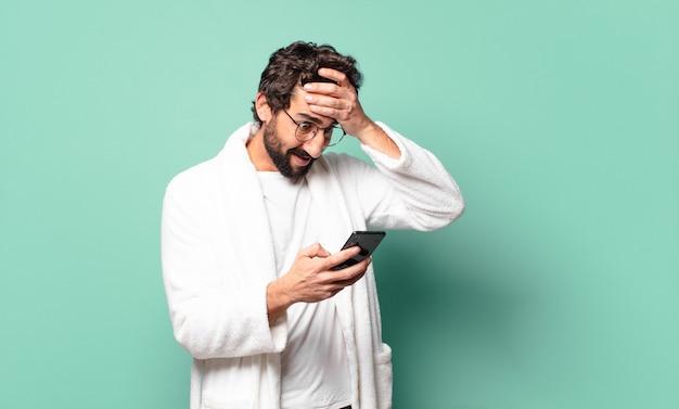 Młody szalony brodaty mężczyzna ubrany w szlafrok używający komórki his