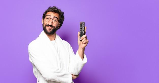 Młody szalony brodaty mężczyzna ubrany w szlafrok z pilotem do telewizora