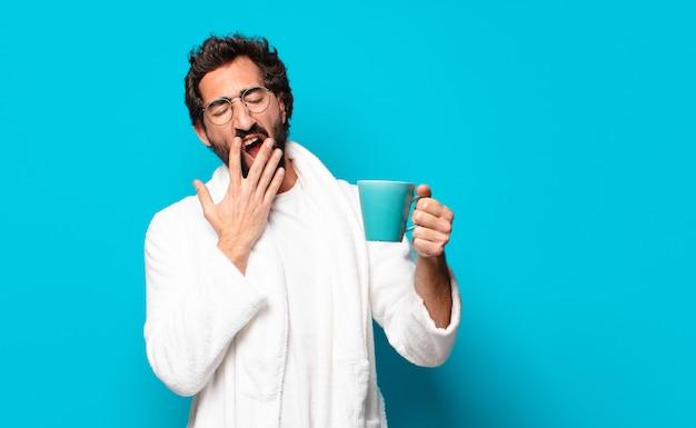 Młody szalony brodaty mężczyzna w szlafroku z filiżanką kawy