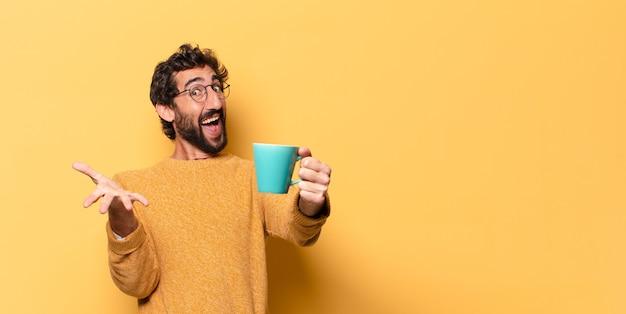 Młody szalony brodaty mężczyzna z filiżanką kawy