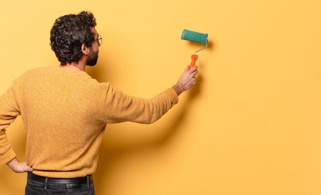Młody szalony brodaty mężczyzna z malowaniem wałkiem i zmieniającym kolor ściany