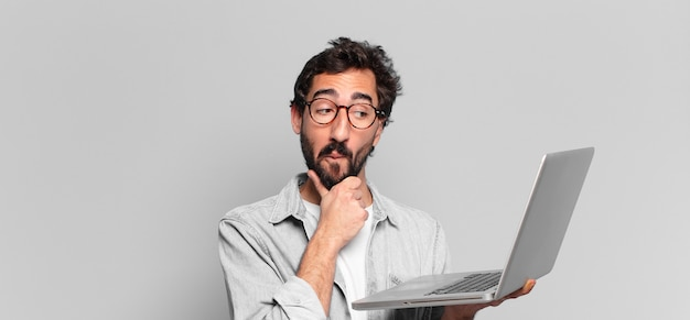 Młody szalony brodaty mężczyzna z myślącym lub wątpiącym w wyrażenie, trzymający laptopa