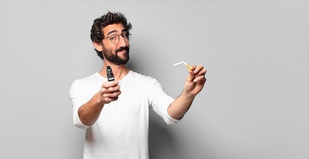 Młody szalony brodaty mężczyzna z papierosem. brak koncepcji palenia
