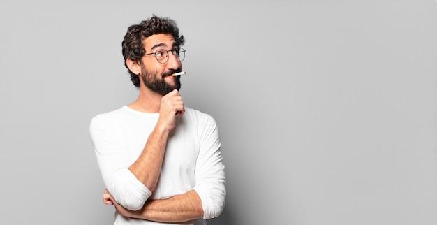 Młody szalony brodaty mężczyzna z papierosem. brak koncepcji palenia.
