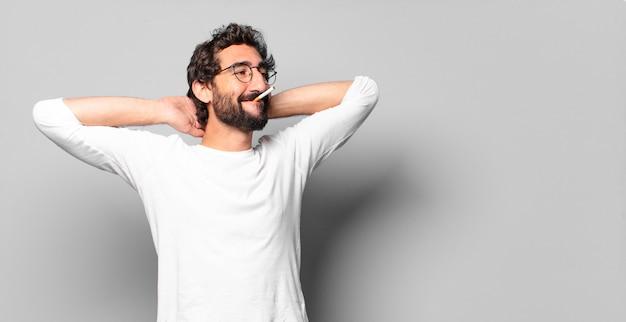 Młody szalony brodaty mężczyzna z papierosem. zakaz palenia.