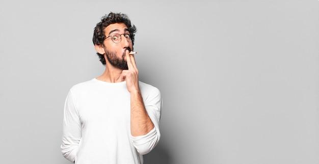 Młody szalony brodaty mężczyzna z papierosem