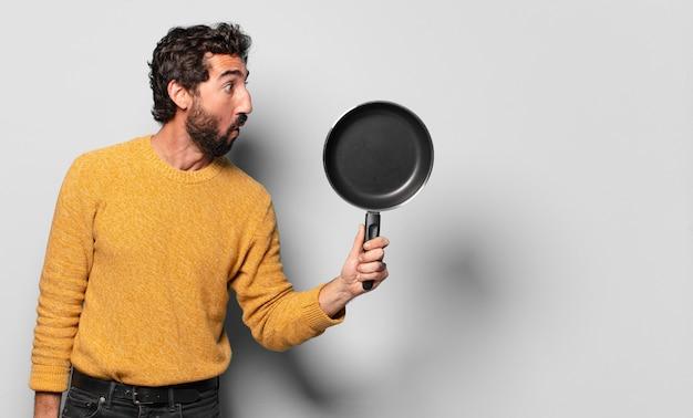 Młody szalony brodaty mężczyzna z patelni. koncepcja kucharza