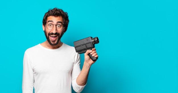 Młody szalony brodaty mężczyzna z super 8 kamerą
