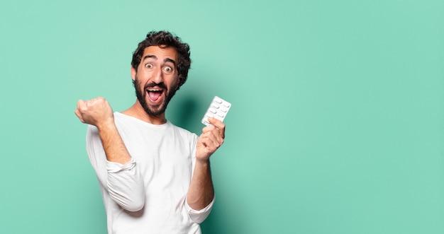 Młody szalony brodaty mężczyzna z tabletką pigułki