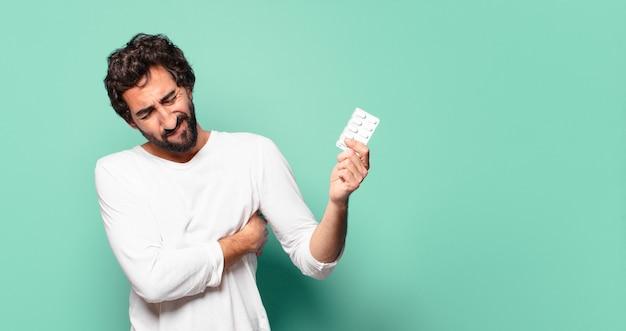 Młody szalony brodaty mężczyzna z tabletką tabletek