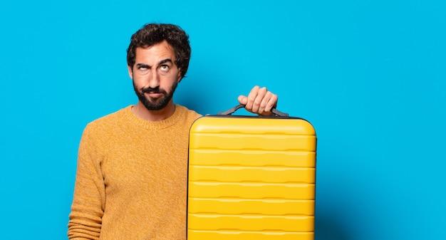 Młody szalony brodaty mężczyzna z walizką
