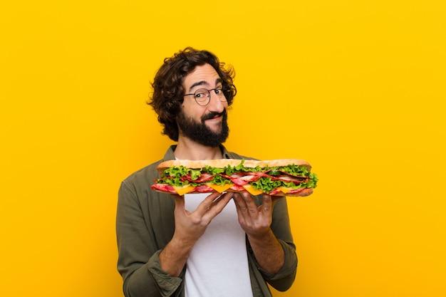Młody szalony brodaty mężczyzna z wielką kanapką.