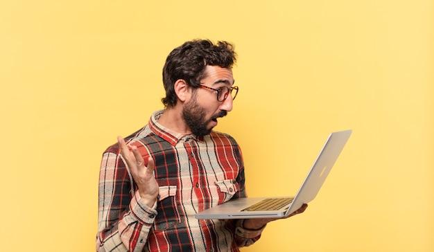 Młody szalony brodaty mężczyzna zaskoczony wyrazem twarzy i laptopem