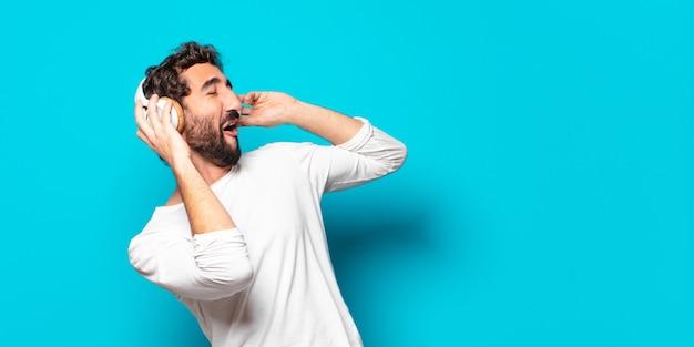 Młody szalony brodaty mężczyzna ze słuchawkami do słuchania muzyki