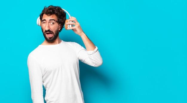 Młody szalony brodaty mężczyzna ze słuchawkami słuchający muzyki