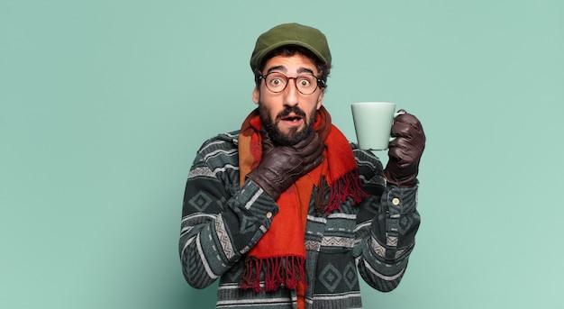 Młody szalony brodaty mężczyzna. zszokowany lub zdziwiony wyraz twarzy i noszenie zimowego ubrania