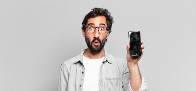 Młody szalony brodaty mężczyzna. zszokowany lub zdziwiony wyraz twarzy. koncepcja ekranu telefonu