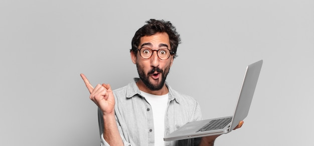 Młody szalony brodaty mężczyzna. zszokowany lub zdziwiony wyraz twarzy. koncepcja laptopa