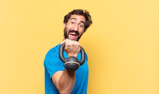 Młody szalony brodaty sportowiec młody szalony brodaty sportowiec szczęśliwy wyraz twarzy i podnoszenie hantli
