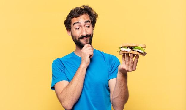 Młody szalony brodaty sportowiec myśli koncepcja ekspresji i diety
