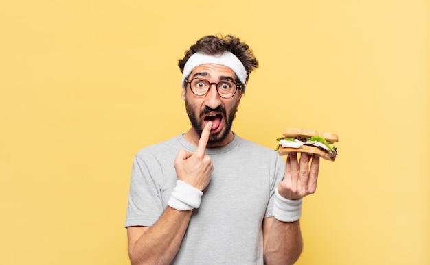 Młody szalony brodaty sportowiec smutny wyraz twarzy i trzymający kanapkę