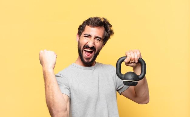 Młody szalony brodaty sportowiec świętujący zwycięstwo i trzymający hantle