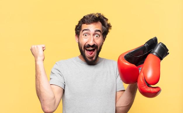 Młody szalony brodaty sportowiec świętujący zwycięstwo i trzymający w dłoniach rękawice bokserskie