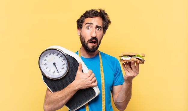 Młody szalony brodaty sportowiec szczęśliwy wyraz, trzymający kanapkę i wagę
