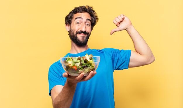 Młody szalony brodaty sportowiec szczęśliwy wyraz, trzymający sałatkę i pokazujący biceps