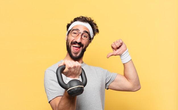 Młody szalony brodaty sportowiec szczęśliwy wyraz twarzy i podnoszenie hantli