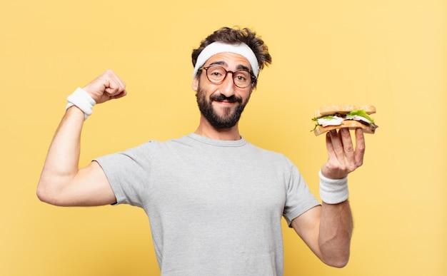 Młody szalony brodaty sportowiec szczęśliwy wyraz twarzy i trzymający kanapkę
