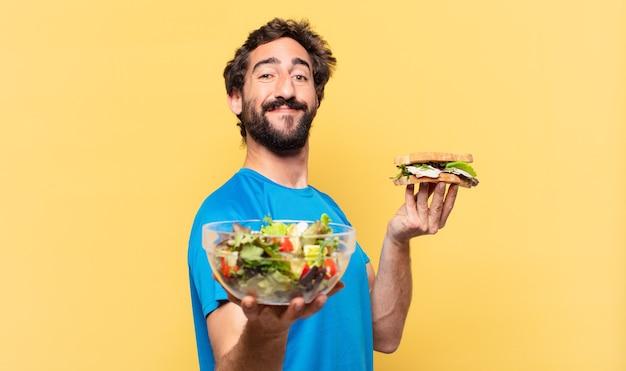 Młody szalony brodaty sportowiec szczęśliwy wyrażenie i koncepcja diety