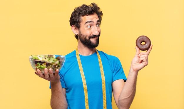 Młody szalony brodaty sportowiec, wątpiący lub niepewny wyraz twarzy, trzymający czekoladowego pączka i sałatkę
