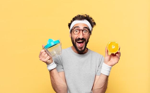 Młody szalony brodaty sportowiec zaskoczony wyrazem twarzy i pomarańczą