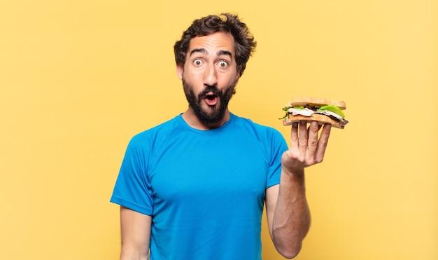 Młody szalony brodaty sportowiec zaskoczony wyrazem twarzy, trzymający kanapkę