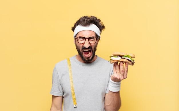Młody szalony brodaty sportowiec zły wyraz twarzy i trzymający kanapkę