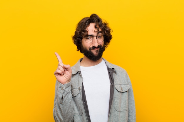 Młody szalony człowiek czuje się jak geniusz, który dumnie unosi palec w powietrze po zrealizowaniu świetnego pomysłu, mówiąc eurekę o żółtą ścianę